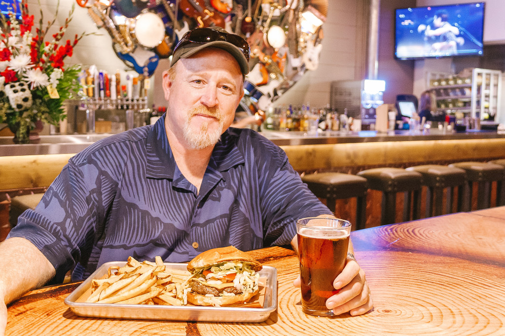 """Co-owner John """"Sparky"""" Pearson sits down behind a burger and a beer in his new restaurant Lone Star Attitude Burger Company. The new burger joint deeply roots its theme as a celebration of Texas music and is located at 113 W. Hickory St. Photo by Edward Balusek / Staff Photographer"""