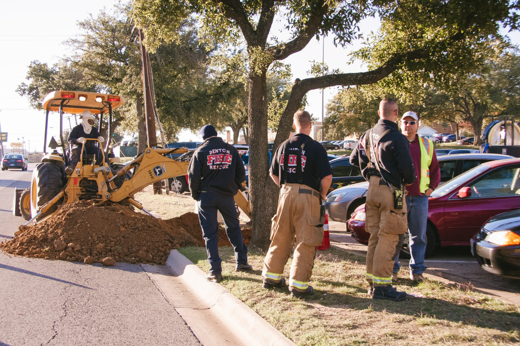 Atmos Energy digs into the sidewalk on W Eagle Dr. to find another area of the leaking gas pipe to clamp shut while Denton Fire Rescue stands by this afternoon. Photo by Margaret Saucedo / Intern Photographer