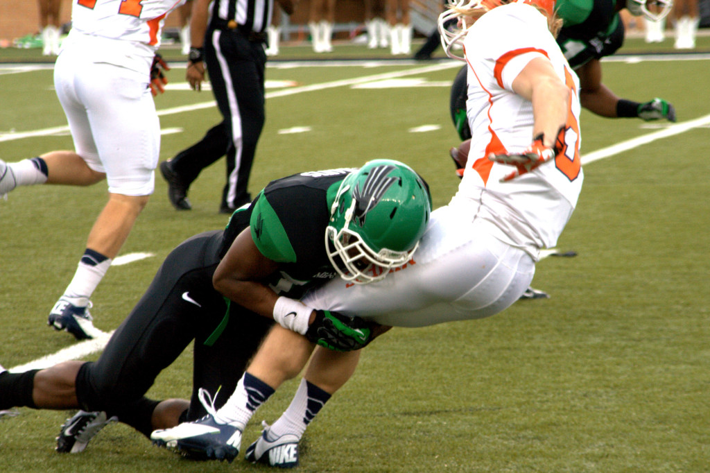Freshman defensive back Chad Davis tackles wide receiver Jim Jones in the first quarter of UNT's 41-7 win over UTEP. Photo by Edward Balusek, Staff Photographer.