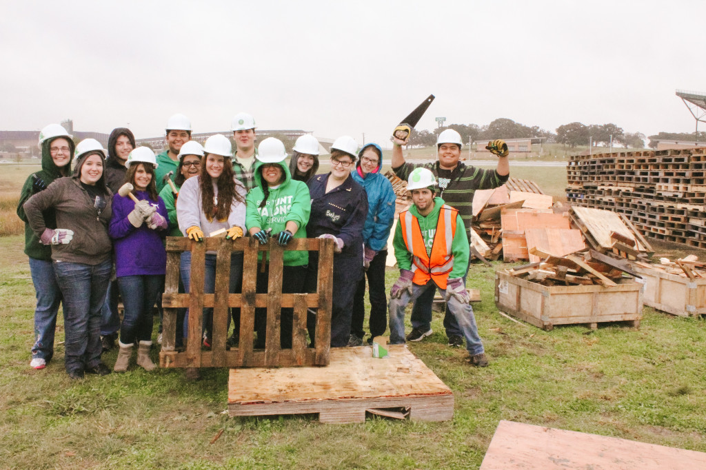 Student workers next to the bonfire pile on Tuesday afternoon. The group has been building the bonfire since Sunday and they have been keeping a 24-hour watch on the structure. Photo by Aidan Barrett / Senior Staff Photographer