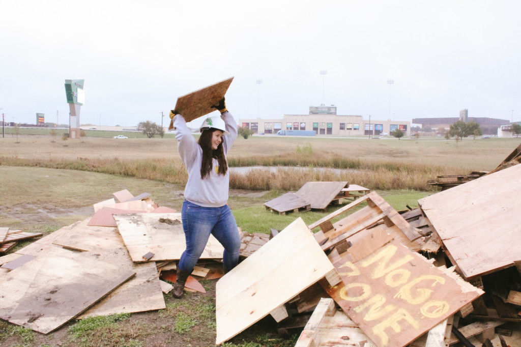 Journalism freshman Paulina De Alva throws a piece of wood onto the no go zone. The no go zone is a pile of wood that the students have yet to build into pallets for the bonfire structure. Photo by Aidan Barrett / Senior Staff Photographer
