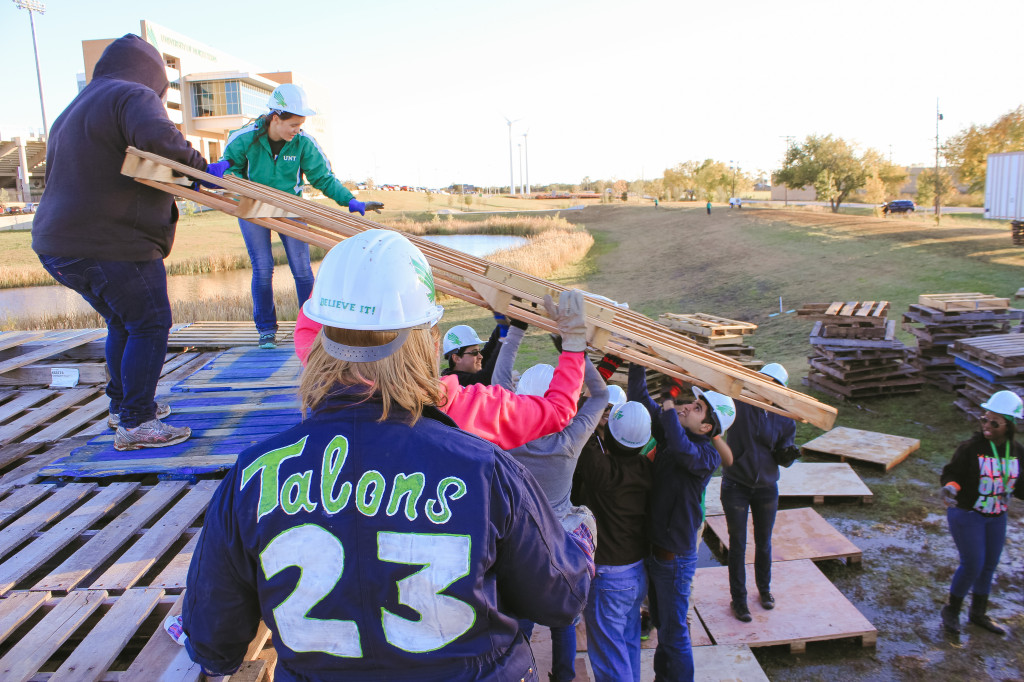 Members of Talons add pallets to the bonfire pile Wednesday evening for the Homecoming festivities. Photo by Aidan Barrett / Senior Staff Photographer