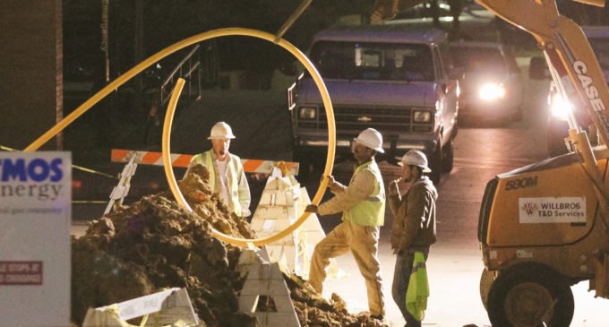 Construction crews repair valve on gas pipe outside Kerr