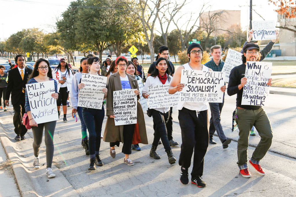 UNT students walking down Welch Street participate the march to celebrate MLK Day with hand made protest signs made by themselves. Photo by Zixian Chen / Senior Staff Photographer