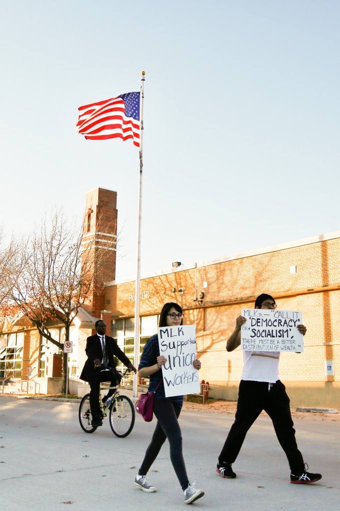 Biology senior Julie Cortes and Spanish senior Richard Velazquez walk by an American flag holding protest signs during the MLK Day march on Monday afternoon. Photo by Zixian Chen / Senior Staff Photographer