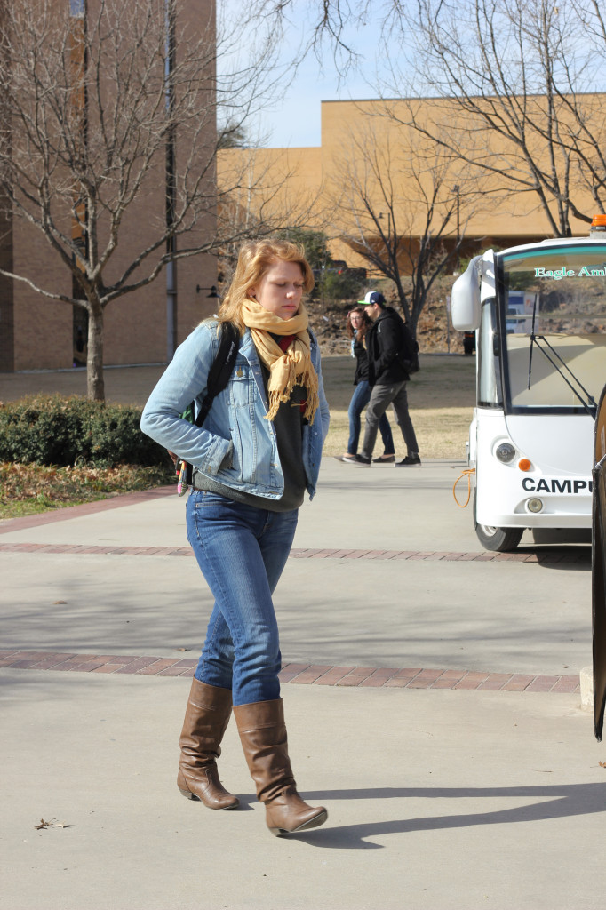 Interior design sophomore Lindsey Torpey walks on campus in the library donning a tan winter scarf, brown leather boots and a jean jacket. Photo by Zach Estrada / Inter Photographer