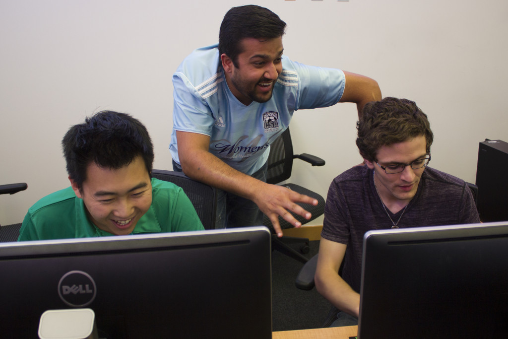 Graduate students Bao Lam, left, Kshitij Menon and Dylan Barnard, right, analyze statistics about the companies the group has talked about in the Buisness Leadership Building on Friday, August 28, 2015. Paulina De Alva | Staff Photographer