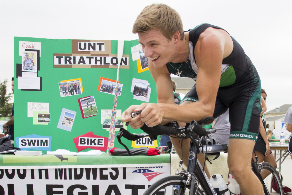 Computer science sophomore Richard Miles rides a stationary bike in front of the UNT Triathlon booth at Mean Green Fling on Thursday, August 20, 2015. Dylan Nadwodny | Intern Photographer