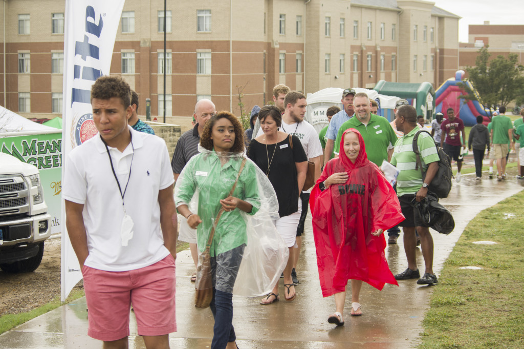 UNT fans try to stay dry on their way to Apogee Stadium for Mean Green's matchup with the Rice Owls.  Matthew Brown | Staff Photographer