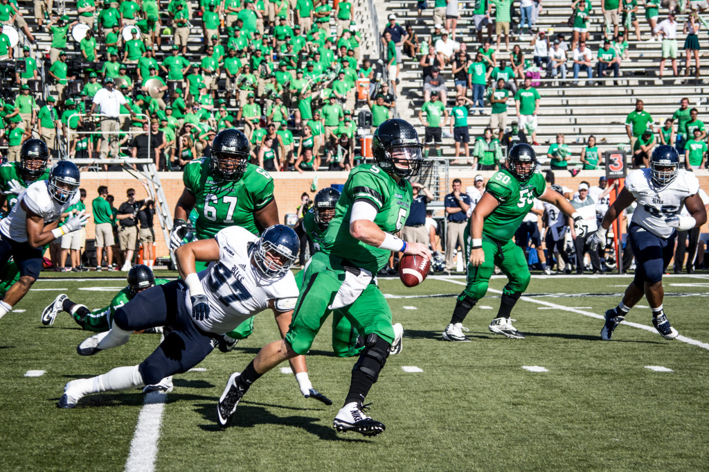 Quarterback Andrew McNulty runs toward the goal line after a snap from his Mean Green teammates.
