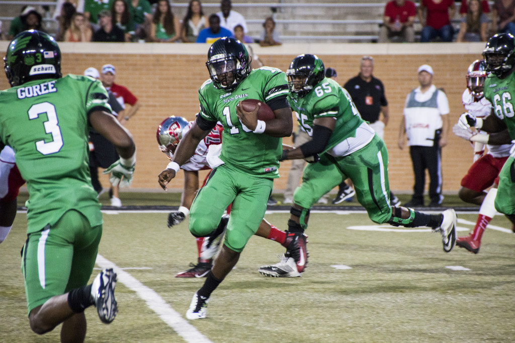 North Texas junior quarterback, DaMarcus Smith (10) jukes out a Western Kentucky defender. Dylan Nadwodny | Staff Photographer
