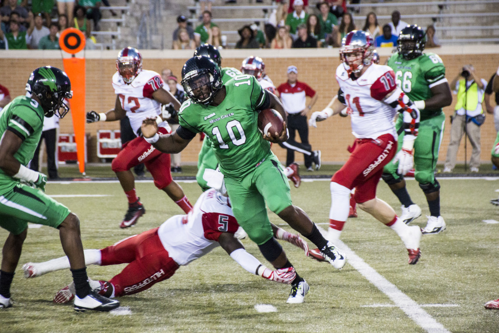 North Texas junior quarterback DaMarcus Smith (10) avoids a tackle from a Western Kentucky defender. Dylan Nadwodny | Staff Photographer
