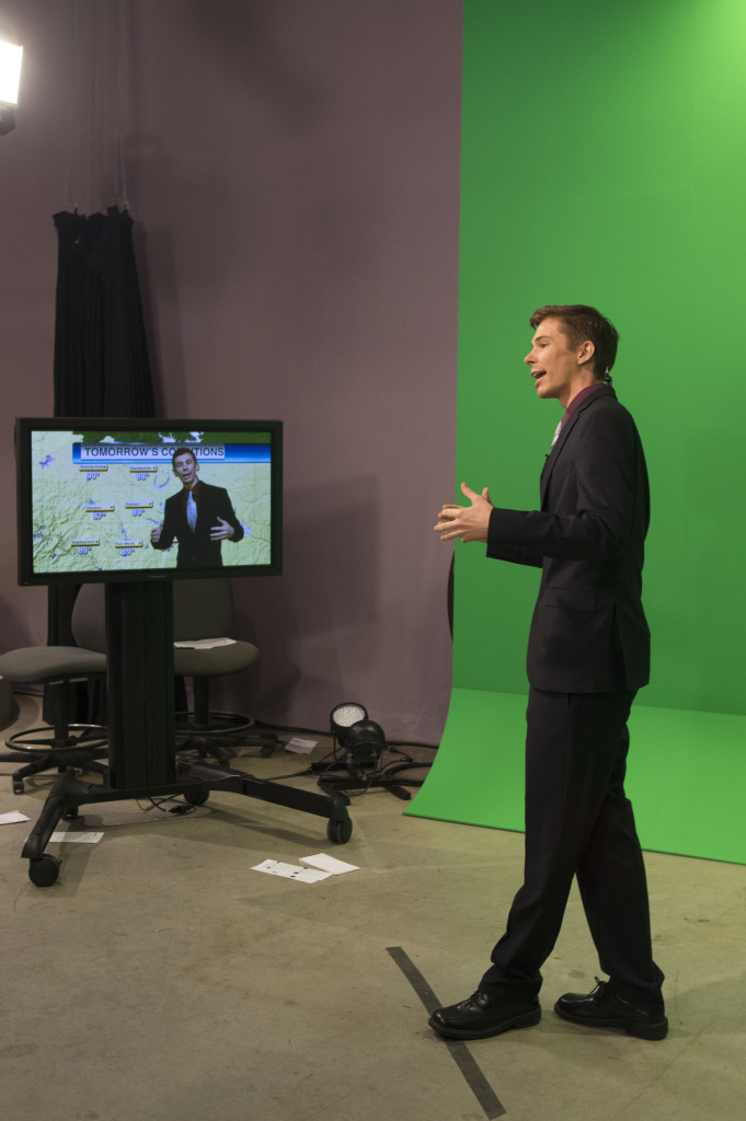 Converged broadcast media senior Evan Nemec stands before a green screen while he delivers the weather report on NTTV's Nightly News. Matthew Brown | Senior Staff Photographer
