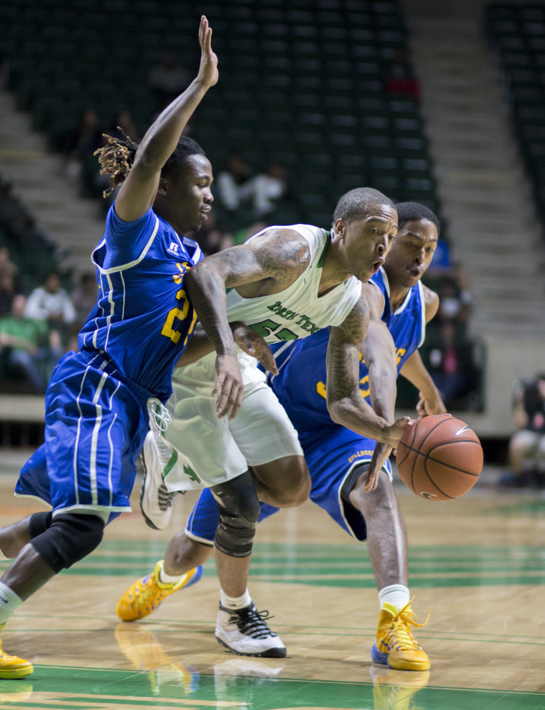 North Texas junior guard JMychal Reese splits Jarvis Christian defenders before passing the ball. Colin Mitchell | Intern Photographer