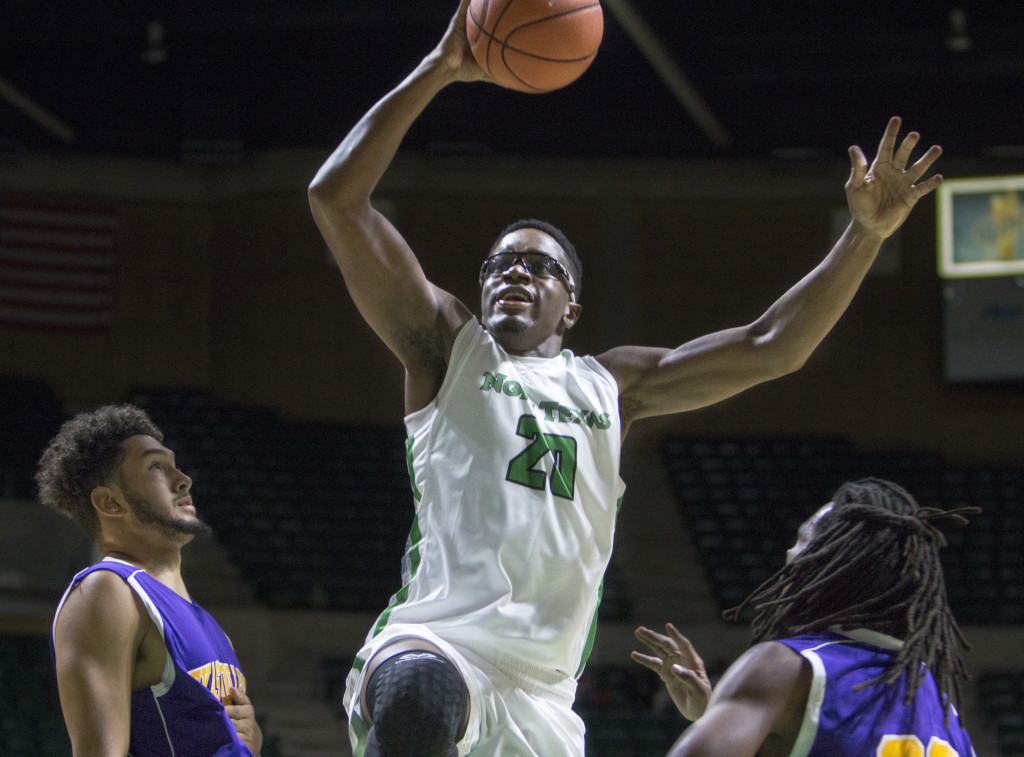 North Texas senior forward Eric Katenda rises over Texas College defenders for a dunk. Nathan Roberts | Contributing Photographer