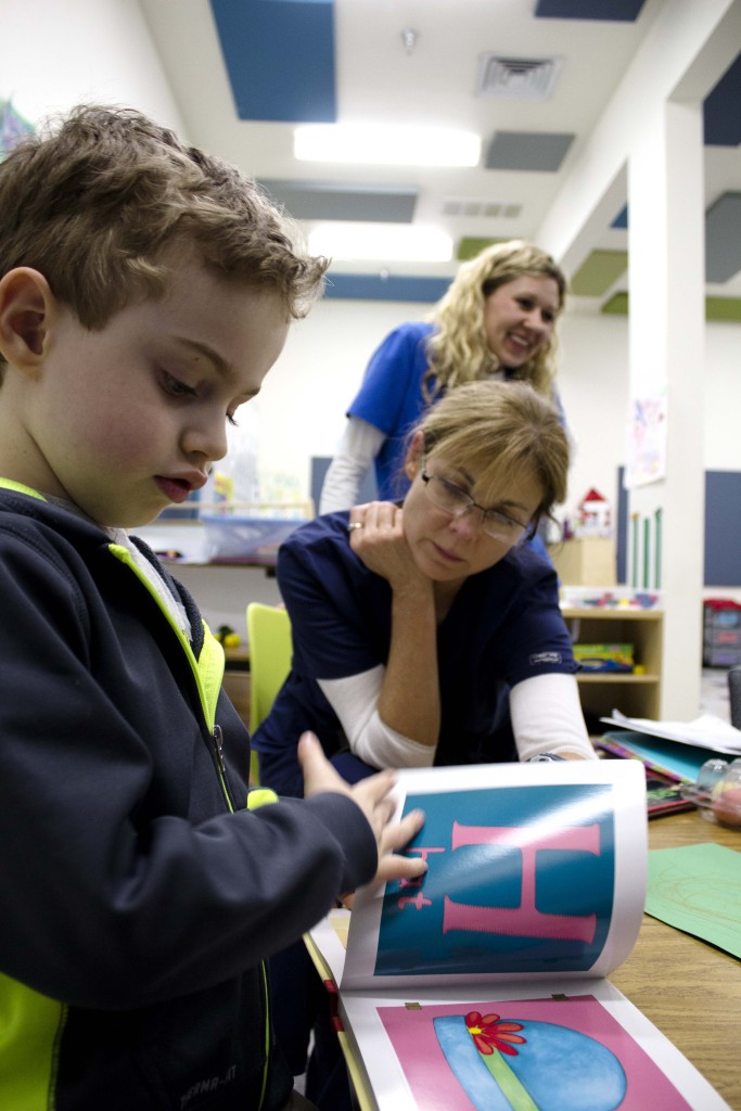 Jackson, a young client of the center, looks through books with his behavioral interventionist, Paige Wilhelm on Tuesday. Jackson prefers to read books during group activity, which can range from building blocks to cutting out shapes. Brittany Sodic | Staff Photographer