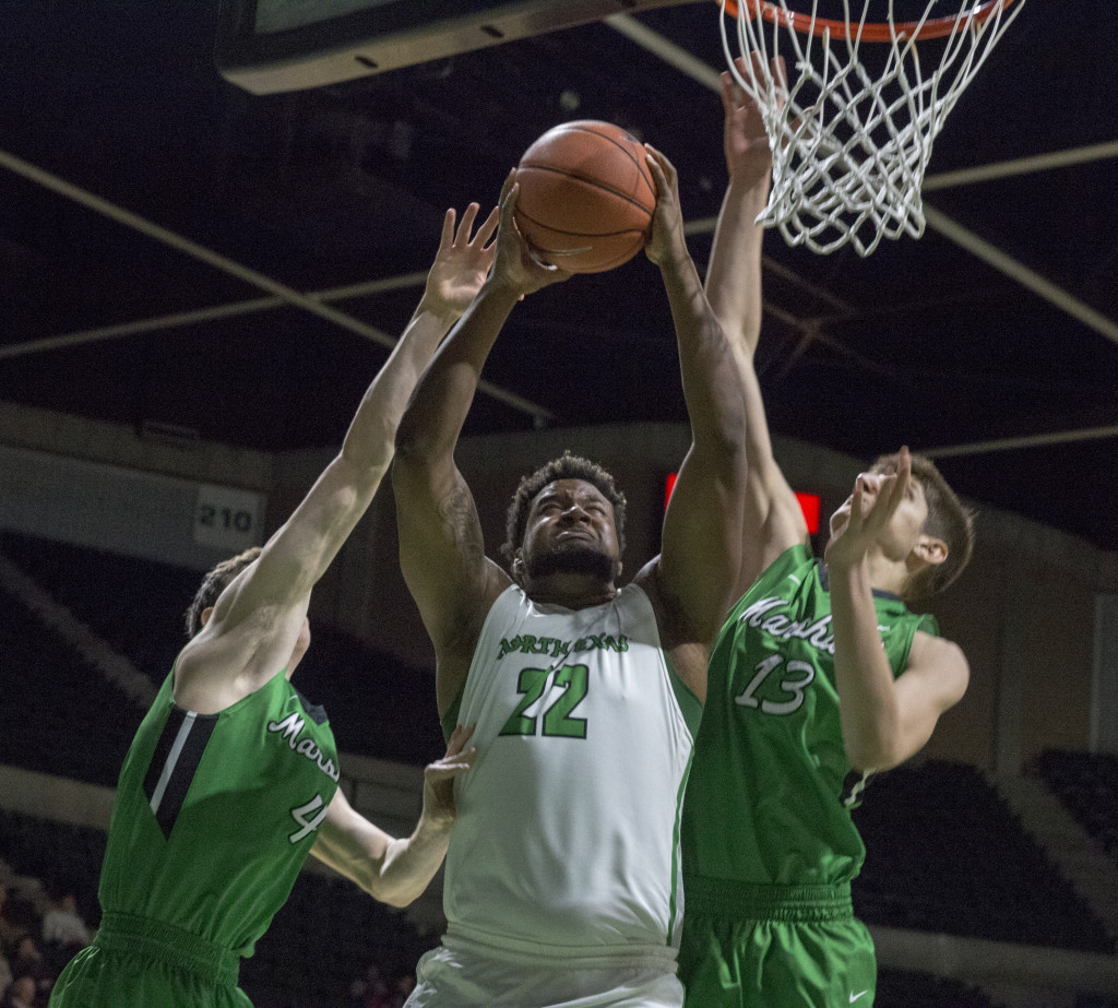 Freshman forward Khalil Fuller (22) goes up for a layup against two Marshall defenders. Colin Mitchell | Senior Staff Photographer