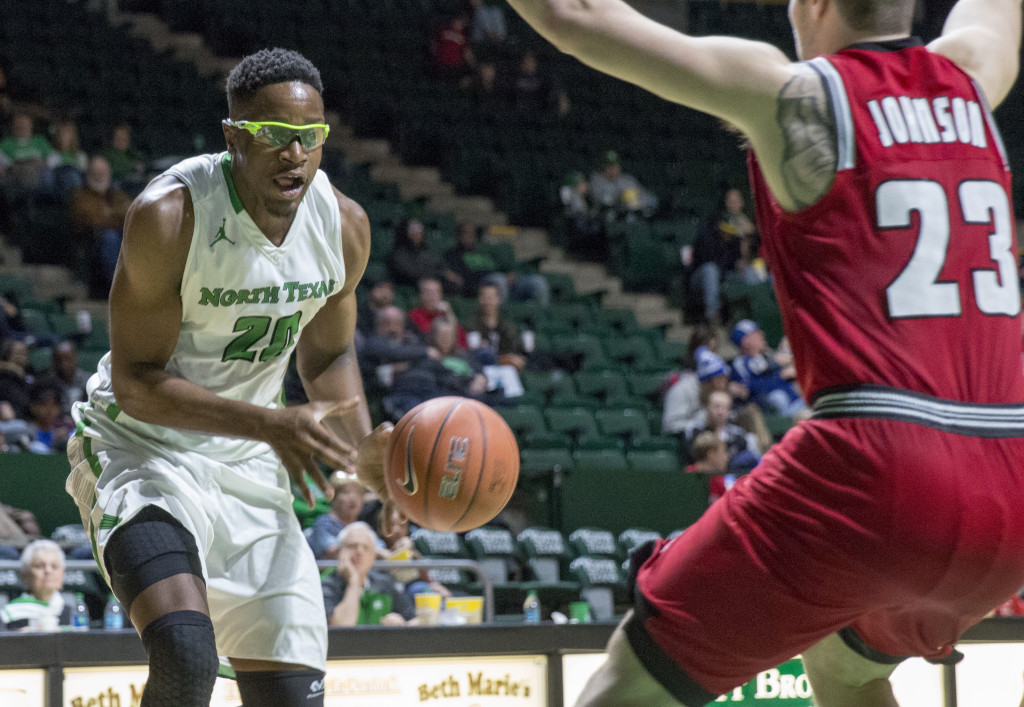 North Texas senior forward Eric Katenda (20) passes the ball while driving the lane against WKU. Katenda 4-4 from the free throw line despite a team 58 percent from the line. Colin Mitchell | Senior Staff Photographer