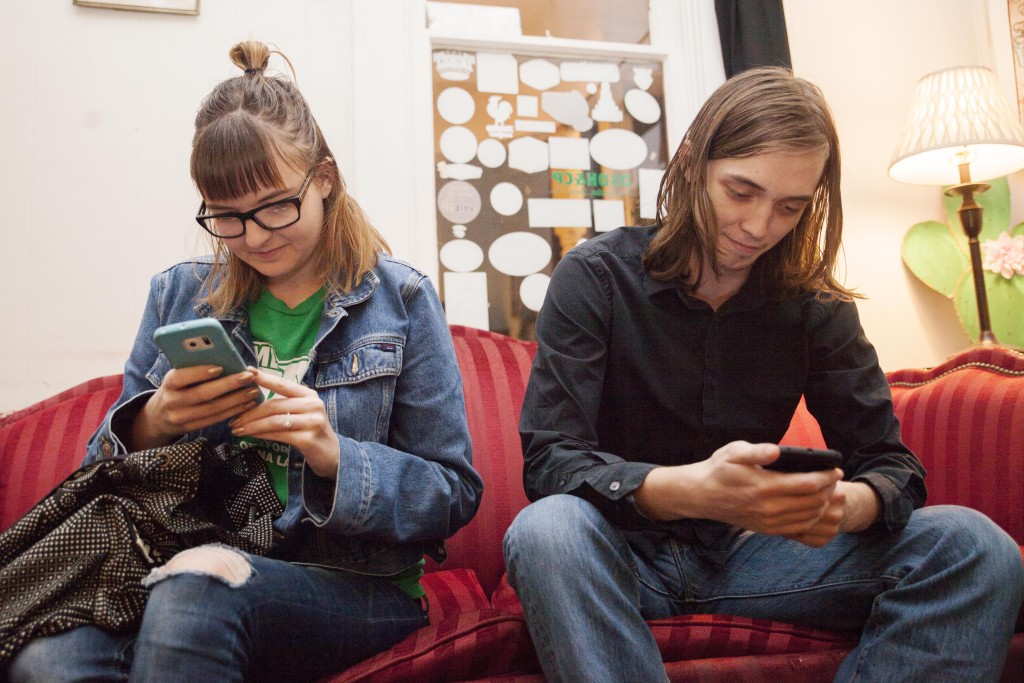 Caroline Turner, left, and Marshall Williams race to look up a current law on their phones to answer a question during Denton Norml social hour at Oak Street Draft House on Tuesday, January 20, 2015. Kristen Watson | Visuals Editor