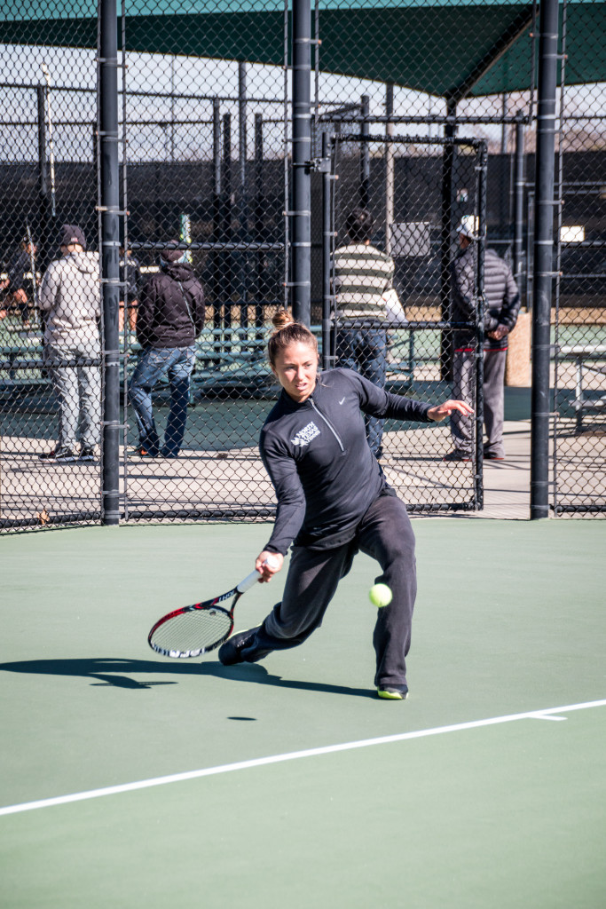 Junior Alexis Thoma digs for a ball while warming up before her singles match. Dylan Nadwodny | Staff Photographer