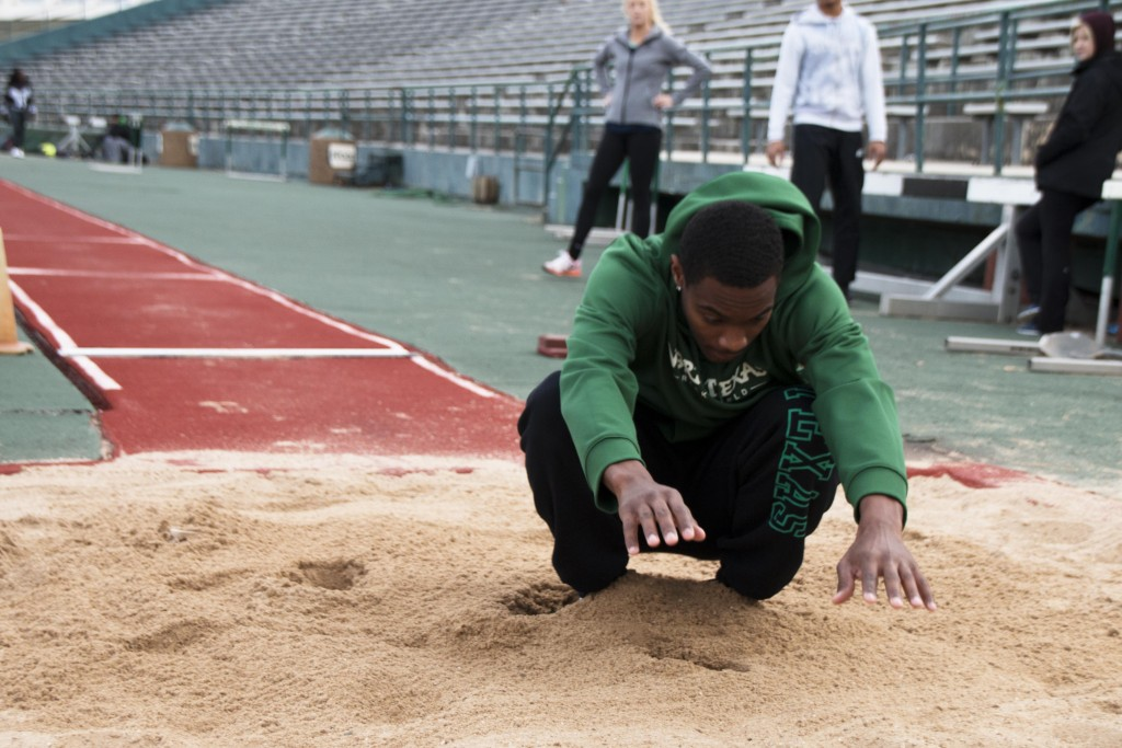 High jumper and senior Eddie Wilcox lands in the sand pit while working on triple jumps at practice. Dylan Nadwodny | Staff Photographer