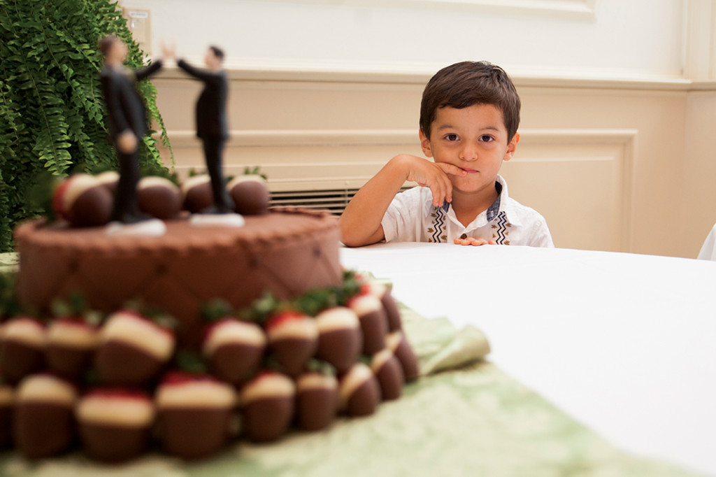 Casey and Tod's son, Eddie, looks longingly at their wedding cake after the two were the first same-sex couple to be married in TWU's  Little Chapel in the Woods. Kristen Watson | Visuals Editor