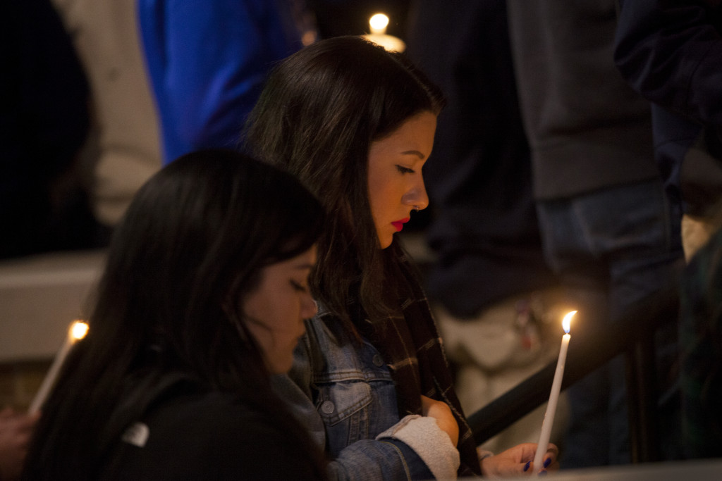 A girl looks at her candle as friends of Sara Mutschlechner share memories of her during the candlelight vigil held by Zeta Tau Alpha in front of UNT's Greek Life Center on Saturday, January 2, 2016. Kristen Watson | DRC