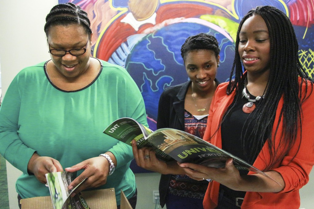 Multicultural Director and Adviser, Cheylon Brown (left in green), looks at new UNT Viewbooks with Olivia Hendersen (orange) and Margarget Humphrey (black jacket),  Wednesday, Feb. 17, 2015. Kaylen Howard| staff photographer. The friends rummage through the pages to find people they recognize.