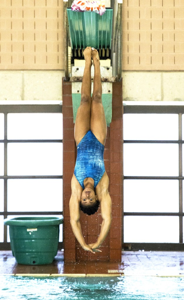 Kinesiology senior Jasmine Abercrombie practices a dive from a three-meter board during practice. Colin Mitchell | Senior Staff Photographer