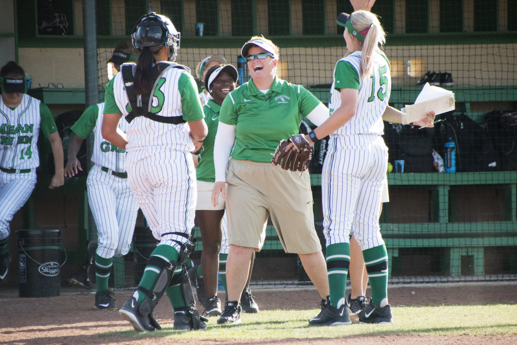 North Texas softball head coach Tracy Kee laughs with senior pitcher Stacey Underwood (15) and senior catcher Bryana Wade (23) after they finish a defensive half-inning against Nicholls State. Dylan Nadwody | Staff Photographer