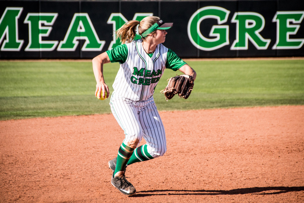 North Texas junior shortstop Kelli Schkade (9) pulls her arm back to throw to first base during the game against Nicholls State in the Mean Green Invitational. Dylan Nadwodny | Staff Photographer