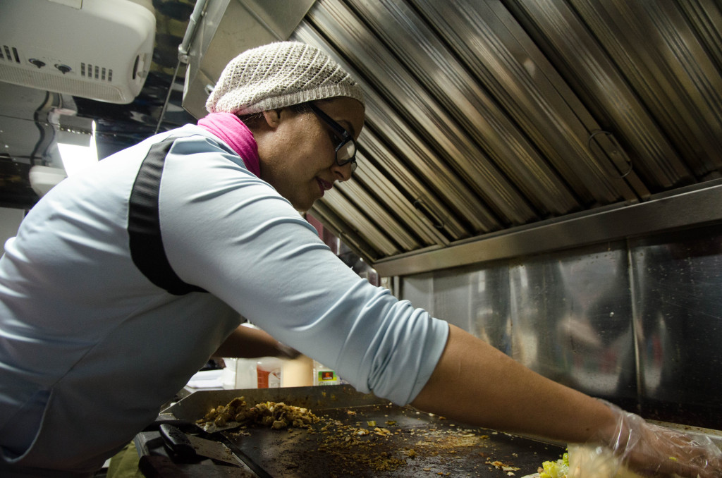 Nazha Oukhallou cooks inside her Mama's Kitchen food truck that is parked on Fry Street. Hannah Ridings | Senior Staff Photographer