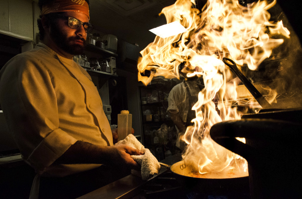 Head chef Tony Neglia moves fast during the dinner rush as he smokes some choppedoninos. Hannah Ridings | Senior Staff Photographer