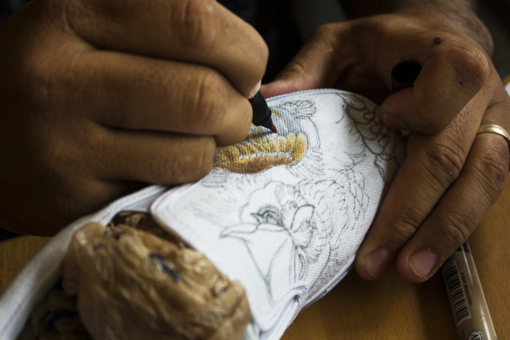"Owner of ""Tattoo My Shoes"" shop Ernie Moreno works on a shoe design for a customer. Moreno first task when customers send him an image they want on their shoes is to turn a flat design into a canvas shoe design. Paulina De Alva 