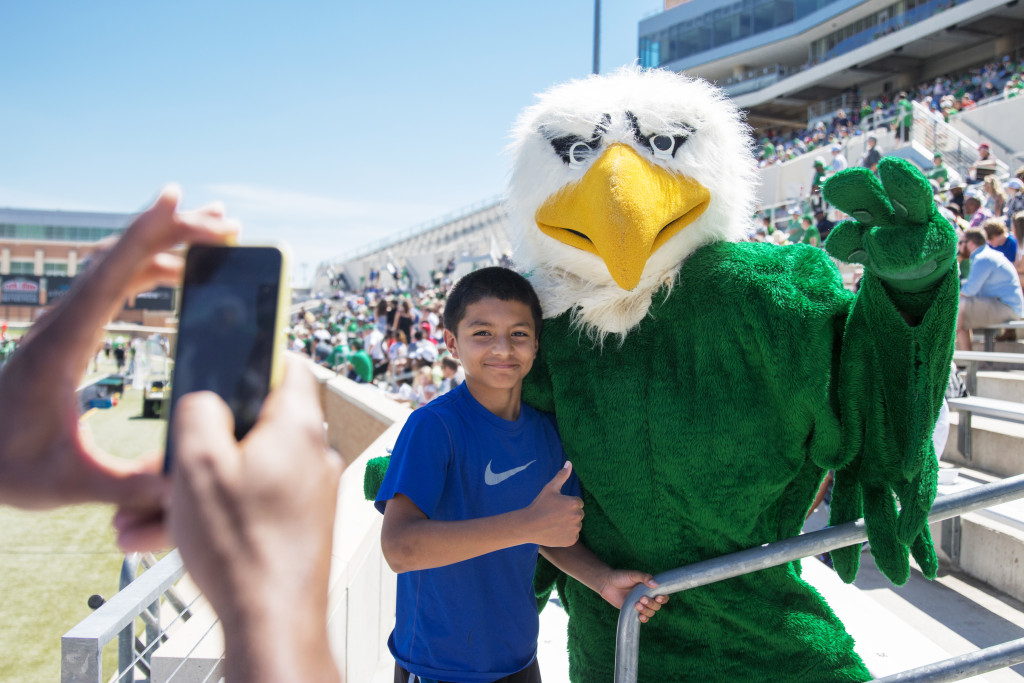 Scrappy poses with a fan in the stands for a photo at the spring game. Colin Mitchell | Senior Staff Photographer