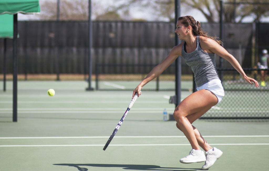 Senior Agustina Valenzuela runs to tap the ball over the net in a singles match. Colin Mitchell | Senior Staff Photographer