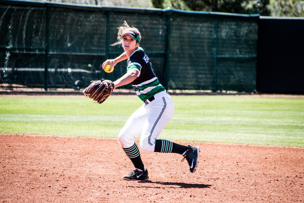North Texas junior infielder Kelli Schkade (9) cocks her arm back to throw a ball to first base to try and throw a Marshall runner out. Dylan Nadwodny | Staff Photographer