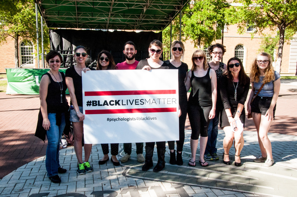 """Psychology Advocates for Social Change hold up their sign before the """"Die-In"""" began on Monday afternoon at Library Mall. Sarah Bradbury 