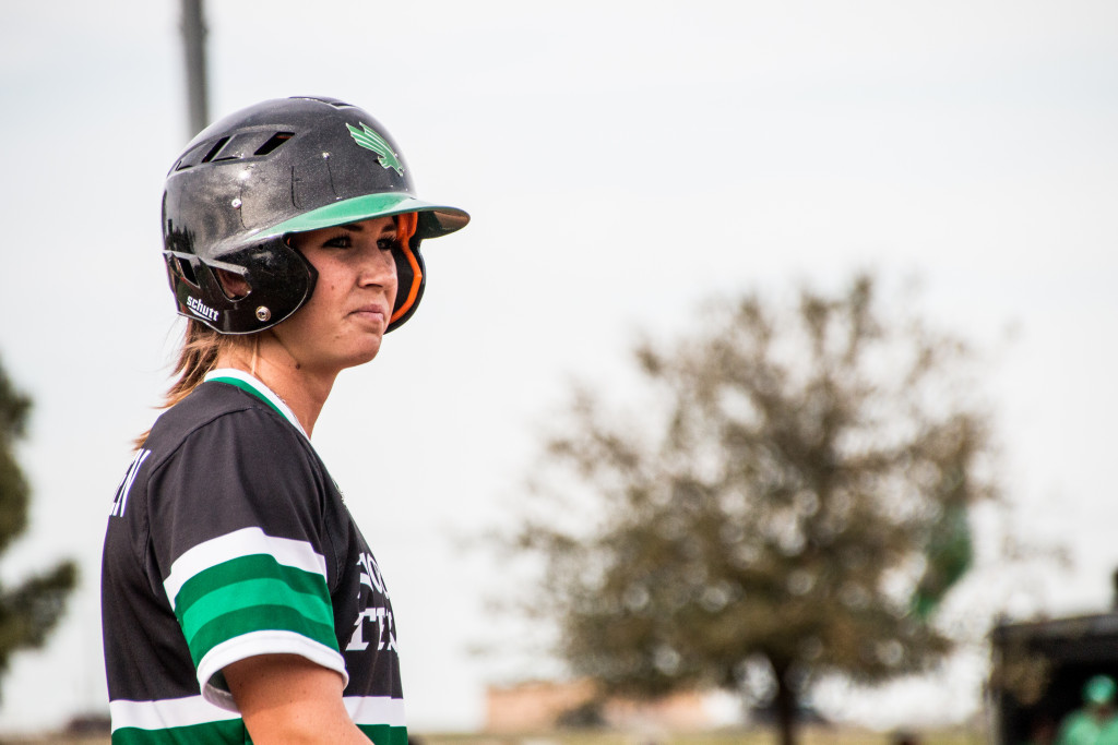 North Texas junior infielder Kelli Schkade (9) looks at assistant coach Natalie Kozlowski after making it to first base against the University of Tennessee-Martin. Dylan Nadwodny | Staff Photographer