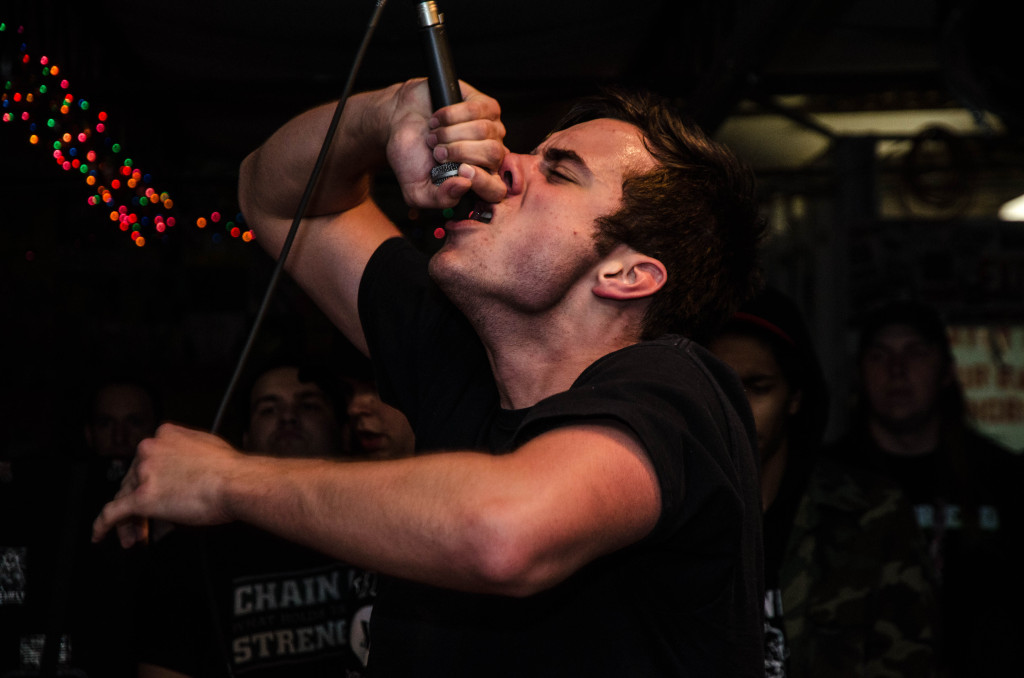 Will Fifer screams into the mic while playing a show with his band Kept in Line at 1919, a DIY venue in Fort Worth. Hannah Ridings | Senior Staff Photographer