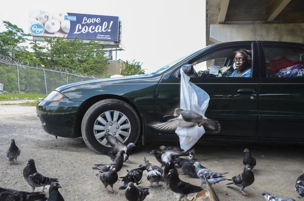 A homeless women parked under the Tent City bridge, feds pigeons some bread crumbs. Hannah Ridings | Senior Staff Photographer