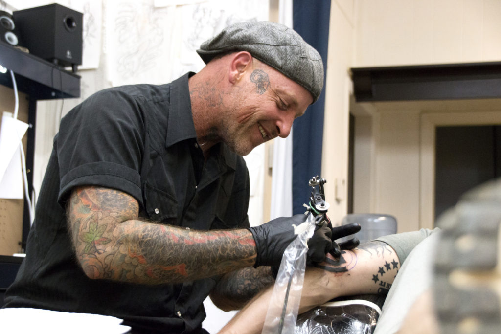 Darian Fulks, Red River Tattoo Company owner, smiles while talking with Justin Crutsinger as he applies the tattoo to Crutsinger's skin.