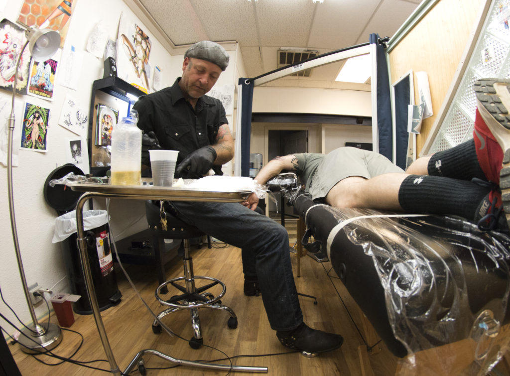 Red River Tattoo Company owner Darian Fulks refills the ink on his needle before working on more of Justin Crutsinger's tattoo.