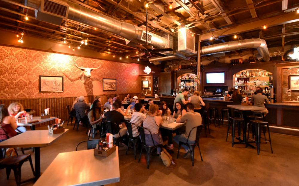 Customers enjoy a variety of dishes inside a dim-lit country like Tex Tapas which opened September 15 on Industrial St. The restaurant specializes in tapas but also offers a variety of dishes. Sanchez Murray | Staff Photographer