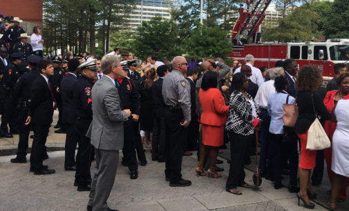 Bystanders outside Meyerson promote love and unity while awaiting presidential visit