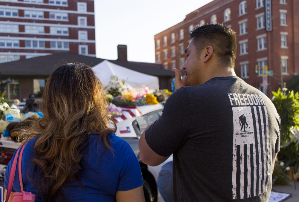 Luis Sone and Maritza Garcia, mourn over the five police officers who died June 7th in Dallas, TX. A memorial of two police vehicles sat outside Dallas Police Headquarters, where people can be seen writing condulgences to the lives lost late Thursday evening, early Friday morning. Tomas Gonzalez | Visuals Editor