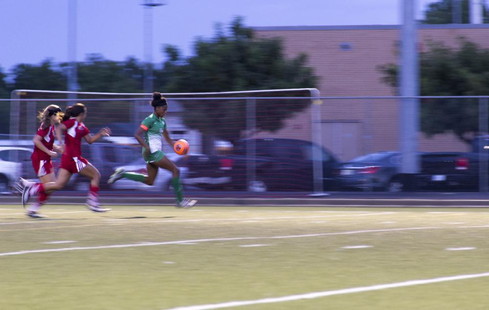 Senior foward, Rachel Holden, takes a run toward goal as she passes two defenders.