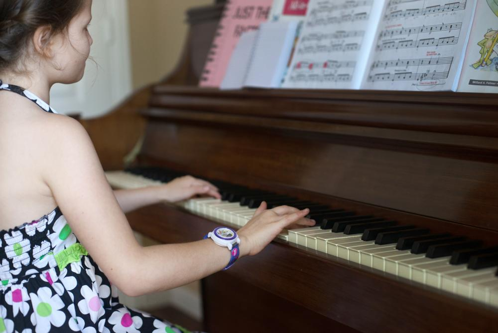 Hallie Barnard shows off her skills on the piano in her home.
