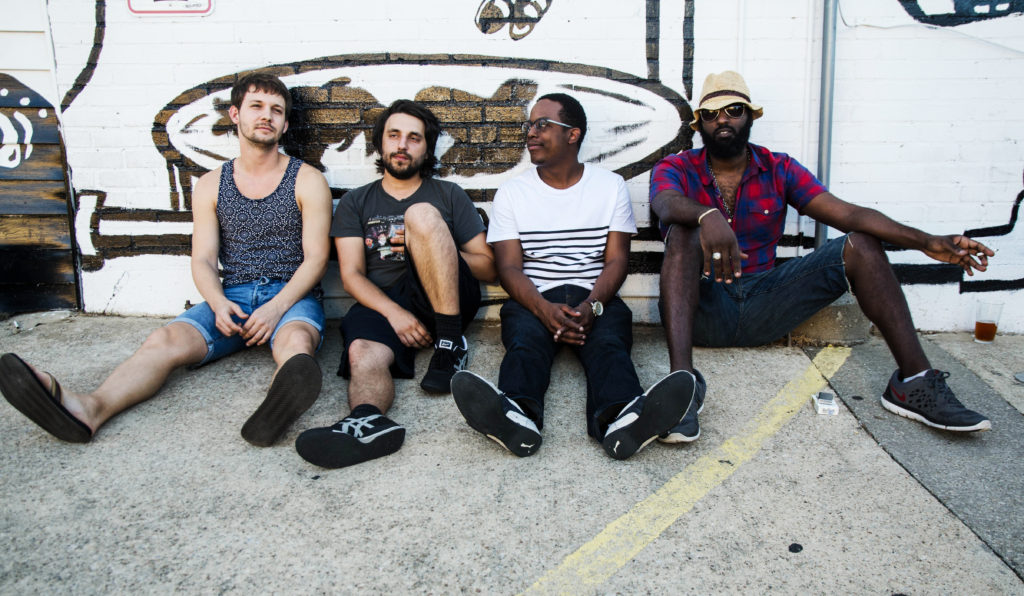 "Connor Veteto (Left) guitar player for The BoomBachs sits with band mates Matt Westmoreland (left middle) keys, Marcus Wheat (middle) keys, and Adonias ""A.D."" Wondwesson (right) outside The Bearded Monk in Denton, Texas."