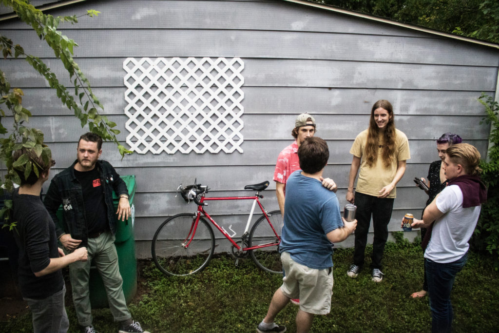 People take a break outside a house venue between sets Sunday for Broketopia. Sara Carpenter